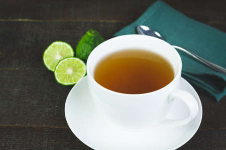Bergamot tea or Earl Grey tea in white cup and fresh bergamot fruit with sliced on brown wooden table. Stock Photo