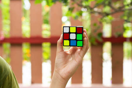 SAMUT-SAKHON, THAILAND - MAY 09, 2021 : Hands of young girl showing the Rubik's Cube puzzle on blur background, Illustrative editorial. Editorial