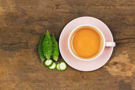 Bitter gourd or bitter melon tea in ceramic cup on wooden background, top view. Scientific name is Momordica charantia. As a whole food and herbs for treating diseases.