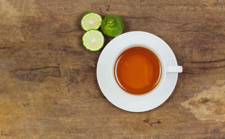 Bergamot tea or Earl Grey tea in white cup and fresh bergamot fruit with sliced on brown wooden table, top view.