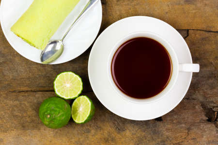 Bergamot tea or Earl Grey tea in ceramic cup and fresh bergamot fruit with sliced on brown rustic wooden table, top view. Stock Photo