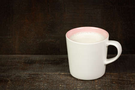 Milk in ceramic mug on wooden table.