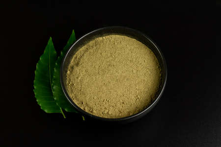 Neem powder in black bowl with neem leaf isolated on black background. Healthcare concept