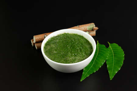 Neem used as ayurvedic medicine on black background. Neem is an excellent moisturizing and contains various compounds that have insecticidal and medicinal properties. Stock Photo