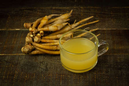 Finger root juice in transparent glass on rustic wooden background, dark tone. Finger root juice as herbal drink for healthcare. Alternative medicine from natur.