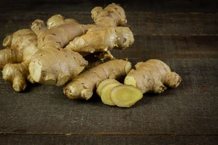 Fresh ginger and sliced on rustic wooden background. The scientific name is zingiber officinale. Herbs for health care concept. Stock Photo