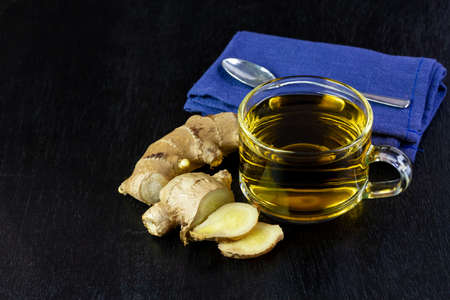 Ginger tea in glass cup and fresh ginger and sliced isolated on black wooden background. The scientific name is zingiber officinale. Herbs for health care concept.