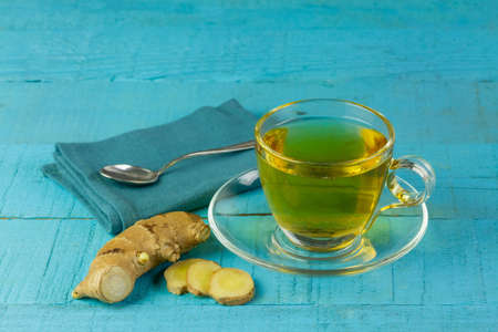 Ginger tea in glass cup and fresh ginger and sliced on blue wooden background. The scientific name is zingiber officinale. Herbs for health care concept.
