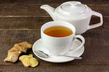 Ginger tea in white ceramic cup and fresh ginger and sliced on wooden background. The scientific name is zingiber officinale. Herbs for health care concept.
