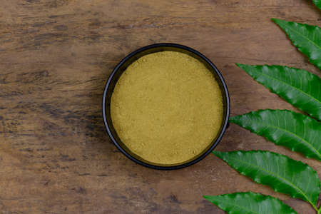 Neem powder in black bowl with neem leaf on rustic wooden background, top view. Healthcare concept