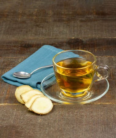Ginger tea in glass cup and fresh ginger and sliced on wooden background. The scientific name is zingiber officinale. Herbs for health care concept. Stock Photo