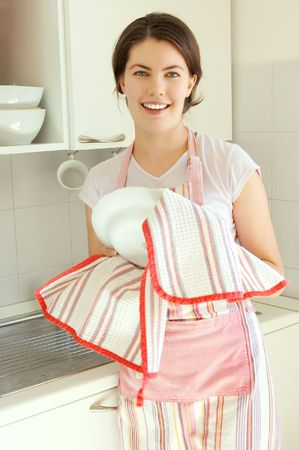 beautiful smiling girl in the kitchen with a plate photo
