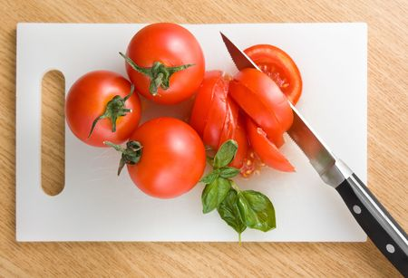 cutting boards: Red tomatoes on hardboard with a knife Stock Photo