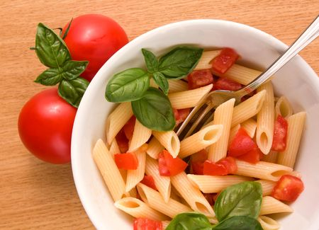 Italian pasta and fresh tomatoes on the table photo