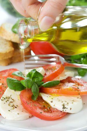 caprese: Oil over caprese salad with tomato and mozzarella
