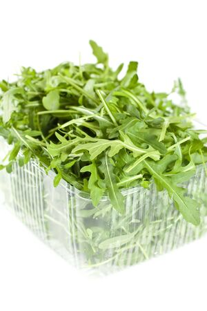 Rucola Leaves In A Plastic Container Isolated On White photo