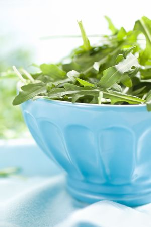 Green Rucola Leaves In A Blue Bowl photo
