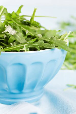 Fresh Green Rucola Leaves In A Blue Bowl photo