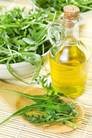 Green Rucola Salad And A Bottle Of Oil photo