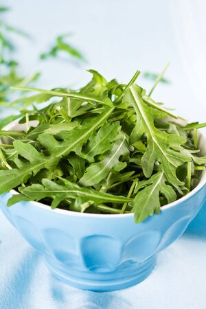 Green Rucola Fresh Salad In Blue Bowl photo