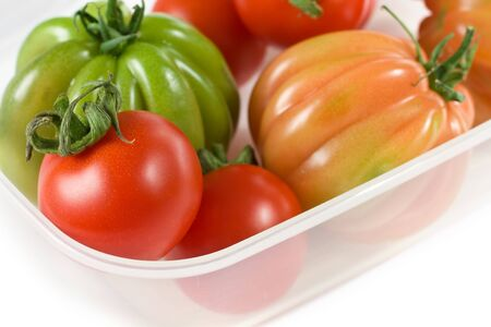 Closeup Of Red And Green Tomatoes On White photo