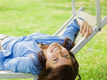 chair garden: Smiling Pretty Girl Lying On A Deckchair Stock Photo