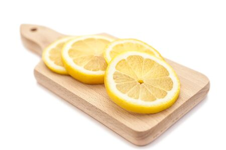 sliced: Sliced juicy lemon on small cutting board isolated Stock Photo