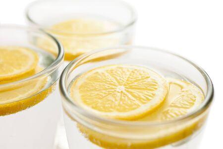 vasos de agua: Fresh lemon slices in sparkilng water glasses
