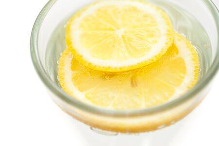 acqua bicchiere: Fette di limone in vetro acqua frizzante, minimalista bevanda sana Archivio Fotografico