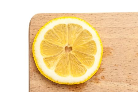 lemon slice: Single slice of lemon on a cutting board, simple and minimalist