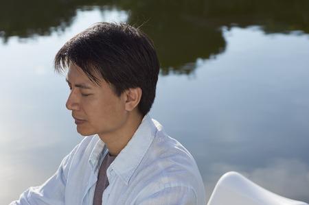 waterside: Chinese man meditating at waterside in the morning