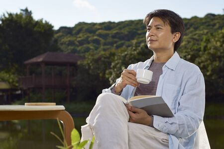 waterside: Chinese man reading waterside holding coffee cup