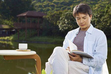 waterside: Chinese man reading waterside  in morning
