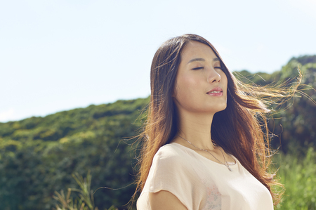 young Chinese beauty smiling in nature with wind blown hair Imagens