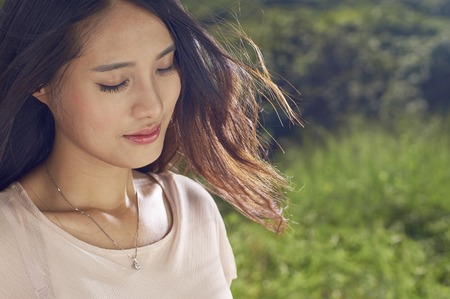 wind blown hair: young Chinese beauty in nature, smiling with eyes closed Stock Photo