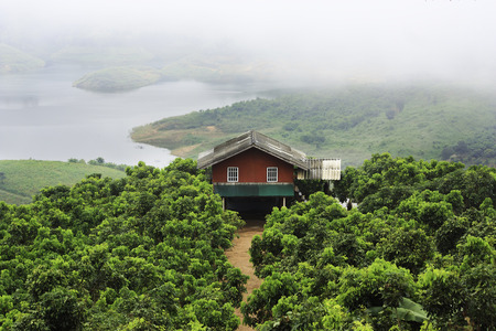 path cottage garden: An red house in mountain on smoke sky, Chiangrai, Thailand.