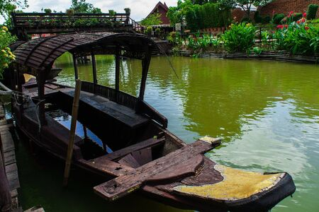 Black Thai wooden boat stay green canal in Ayutthaya, Thailand. Stock Photo