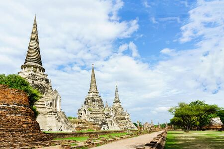 Ancient pagodas on red brick floor step are Ayutthaya, Thailand. This have tree and blue sky be background and ground on foreground of picture. 新闻类图片