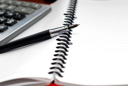 media equipment: Pen and calculator on notebook