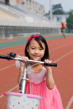 Asian little girl and bicycle photo