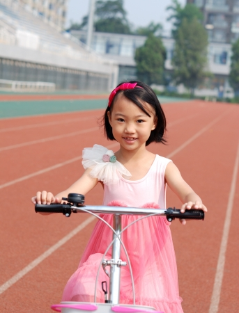Asian little girl riding a bicycle photo