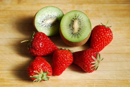 Strawberry and cut by a kiwi on a chopping board photo