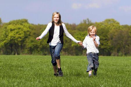 romp: Sibling romp outdoors Stock Photo