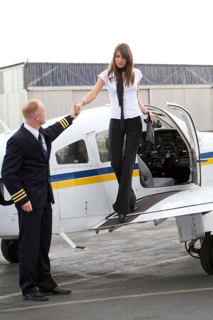 A pilot helps a young, successful and attractive woman on or off the plane from the private photo