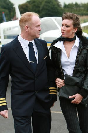 Pilot and young woman in front of a private airplane photo