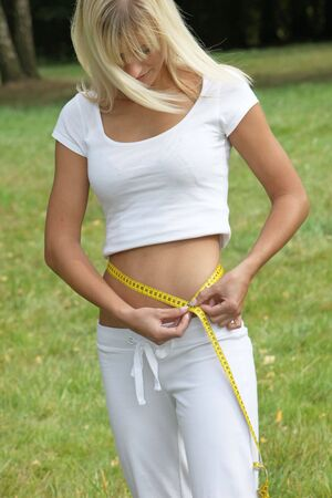 circumference: Sporty, young woman measuring waist circumference with a tape measure in Elegant Sportswear