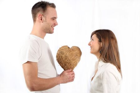 Young man handed smile of a young woman a heart made of straw and both Stock Photo - 6437470