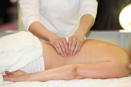 massage table: A woman receives a massage - you lies relaxed on a massage table. The hands of the masseuse masi back.
