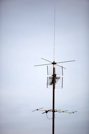 cb phone: A television antenna on a roof against a blue sky