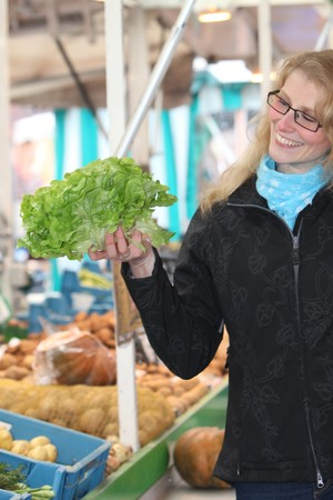 young woman smiling at a market considered a head of lettuce with a basket